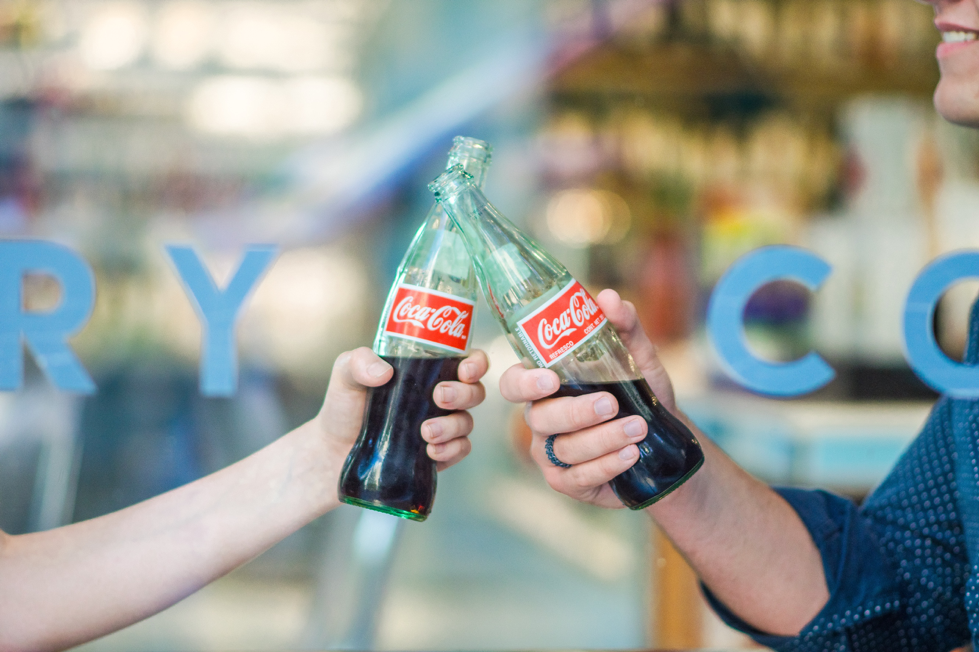 Two people cheersing coke bottles