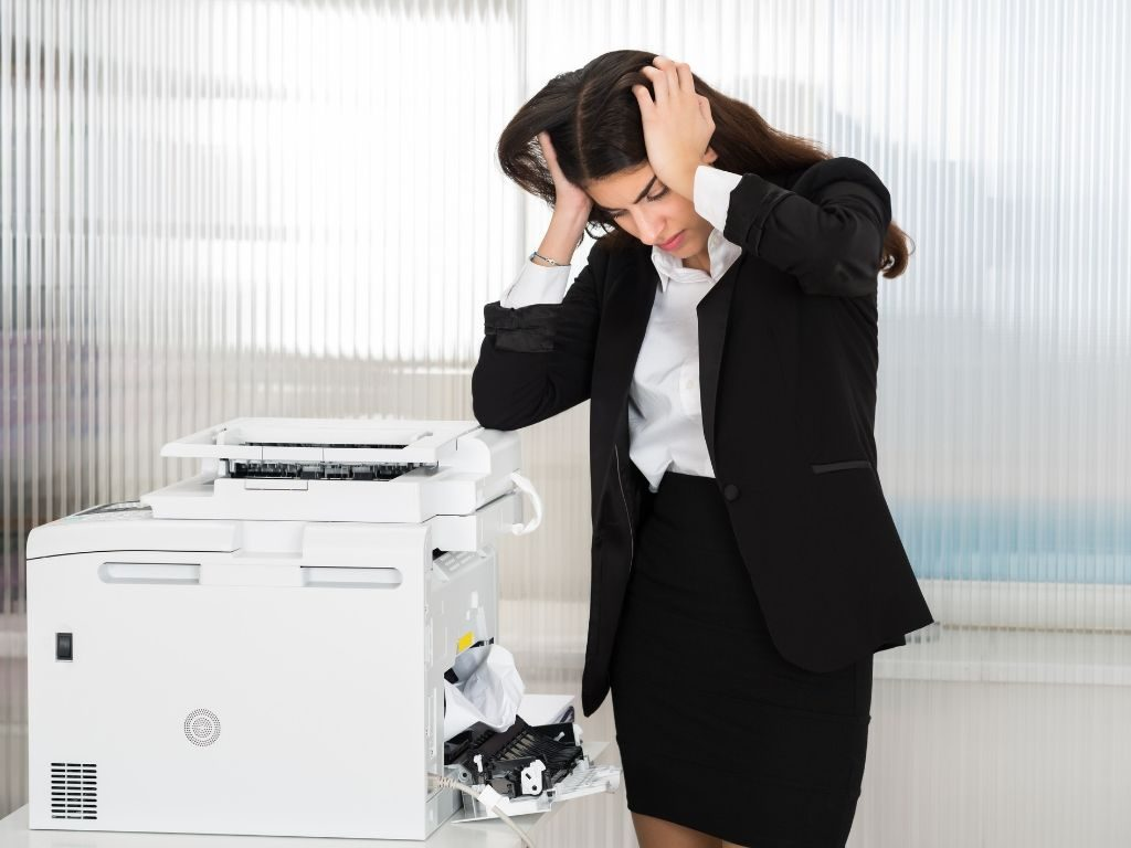 A woman standing next to a printer holder her head in frustration.